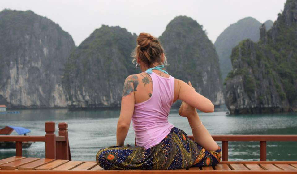 A woman in a sitting pose faces away towards water and mountains.
