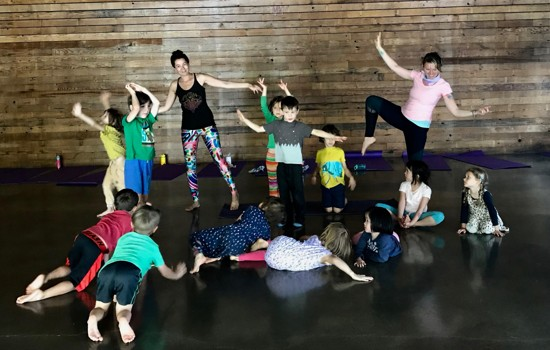 A group of children participating in a playful yoga exercise.
